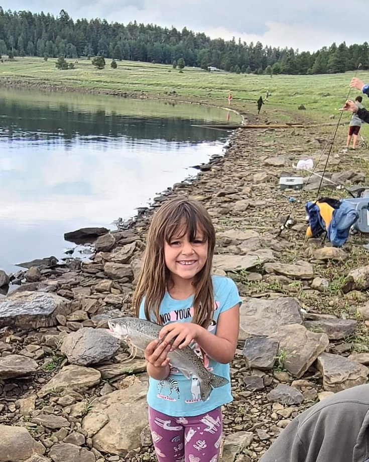 smiling girl holds fish she caught at Arizona Outdoor Adventures