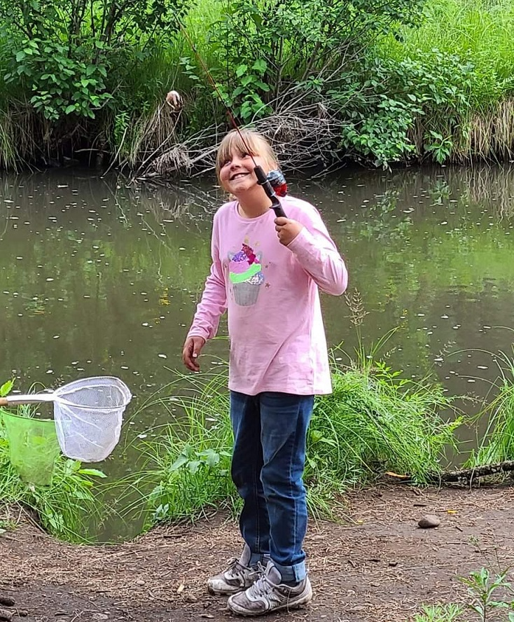 Smiling girl learns how to fish