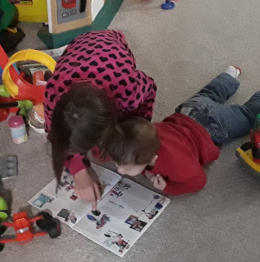 Madeline reads to a younger child via the Life Tools Foundation