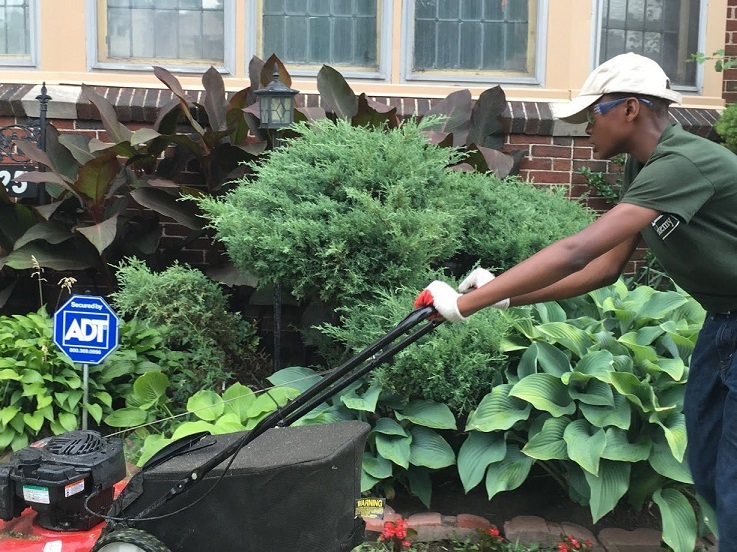 Participant in The Lawn Academy doing community service for seniors by mowing lawns