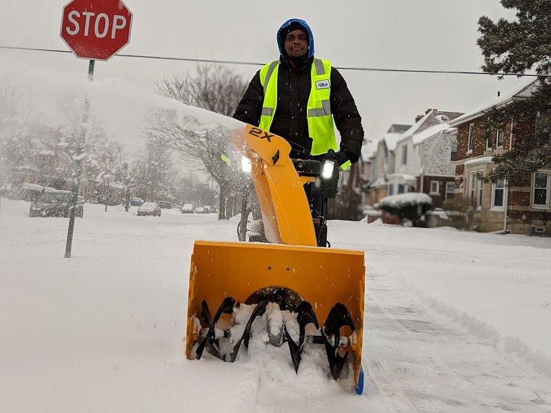 Participant in The Lawn Academy clears snow for seniors